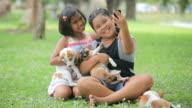 girls and puppy in the garden