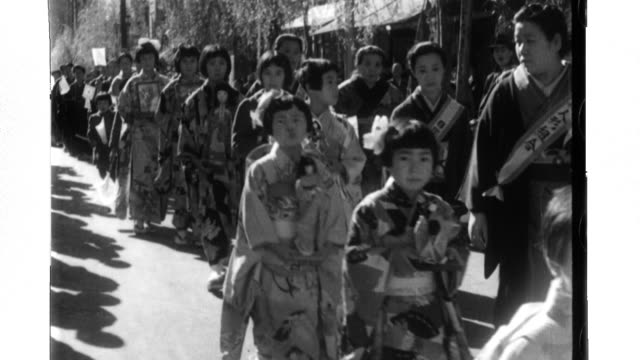 Girls and women from the Kanagawa Doll Makers Association hold Japanese dolls as they march to the German Consulate where they present the dolls to...