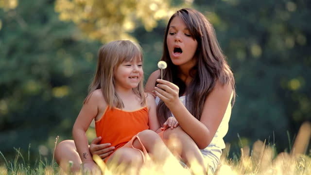 Girls Blowing Dandelion Seeds In the Park