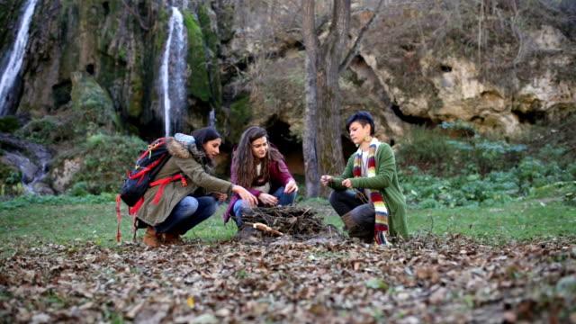 Meisjes verzamelen brand Woods In de natuur