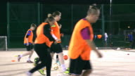 A girls football team practise dribbling in a line during training.