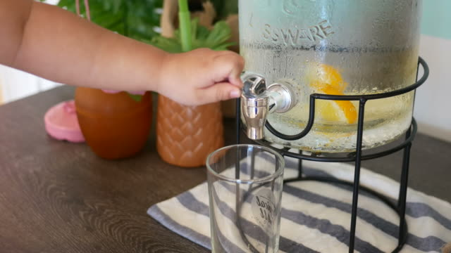 girl's hand press a faucet of water cooler