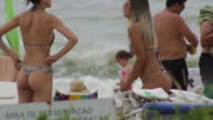Girls in bikini talking at the beach