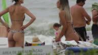 Girls in bikini talking at the beach