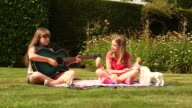 Girls in garden playing with dolls & playing with guitar