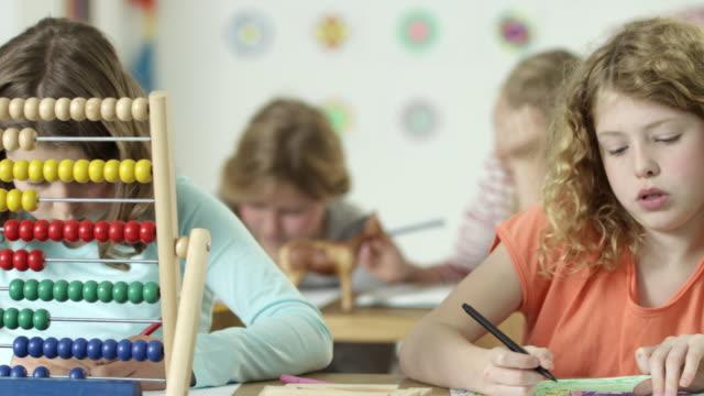 girls in school - adding machine on school desk