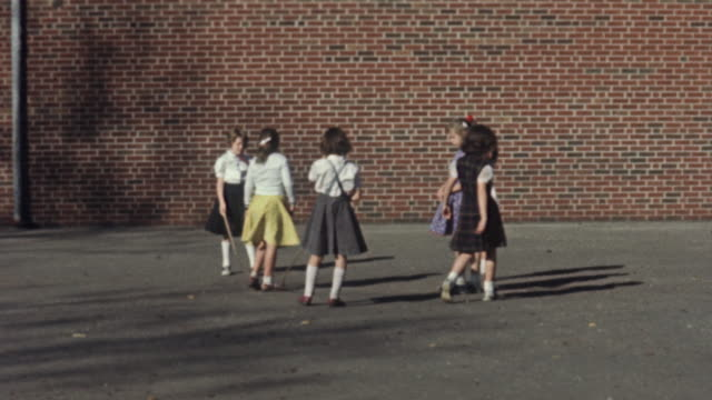 1956 WS Girls jumping rope in schoolyard / USA
