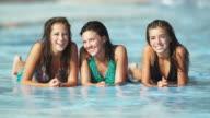 girls lying down in a pool