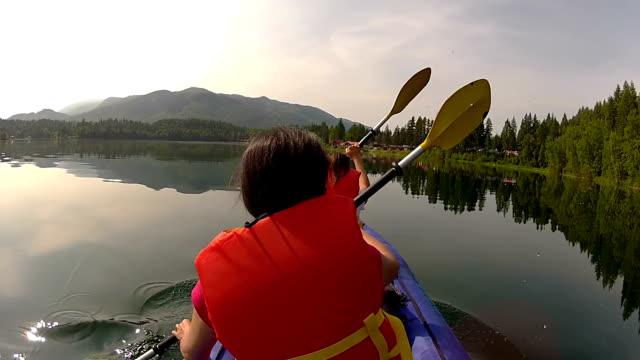 Girls paddling Kayak across a lake