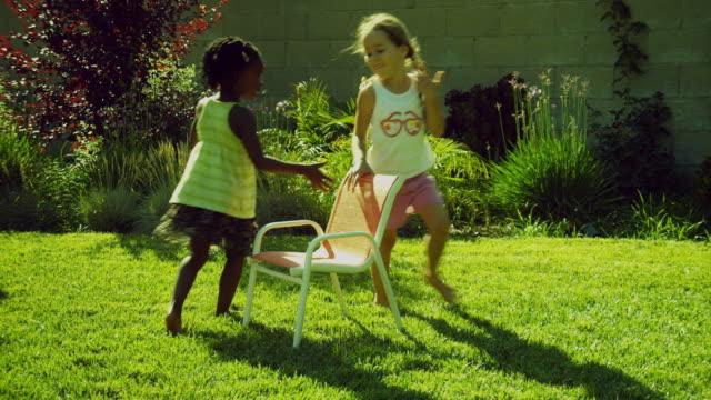 MS Girls (2-5) playing musical chairs in garden / Burbank, California, USA