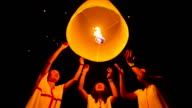 Girls release floating lanterns to the sky.