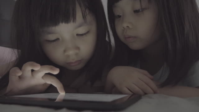 Girls using tablet in bed