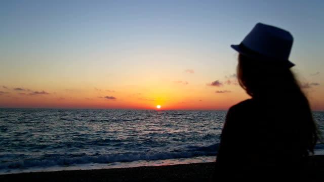 Girls watching sunset over sea