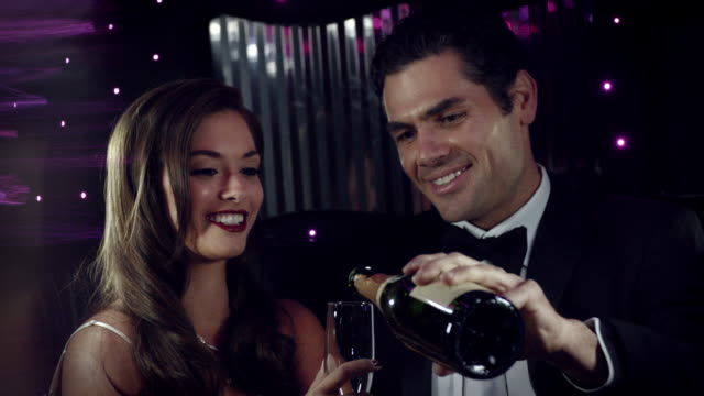 Glamorous couple pour champagne and clink glasses in backseat of limousine at awards show