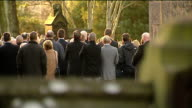Funeral held for three victims from same family Church seen beyond trees Mourners gathered outside church BV Mourners outside church listening to...