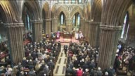 Memorial service to mark first anniversary crash Congregation bow heads for moment of silence / family members place candles on altar / woman and two...