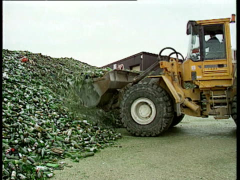 Glass bottles being processed Piles of glass bulldozer scoops up glass huge mountains of glass at landfill site Garbage trucks dumping rubbish into...