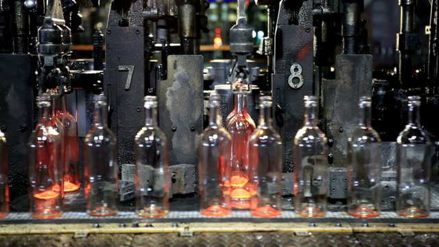 Glass factory. Bottle production machine. Close up.