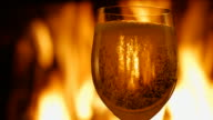 Glass of champagne on the background of fire from the fireplace