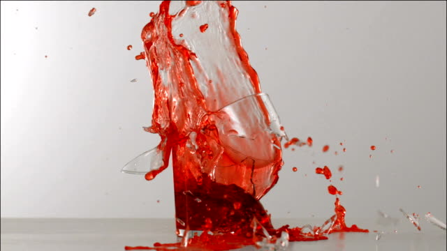 Glass of cherry juice exploding in slow motion
