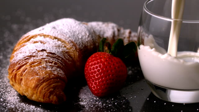 Glass of milk being poured next to strawberry and croissant
