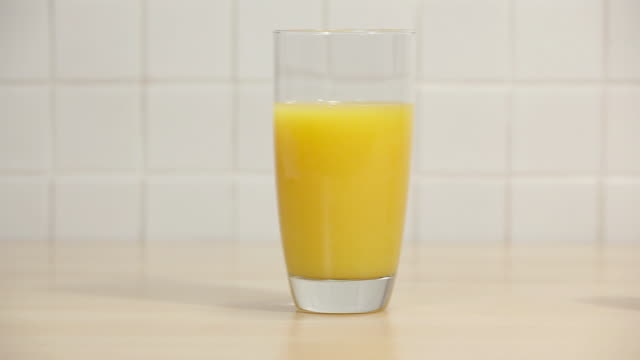 Glass of orange juice and vitamin c tablets