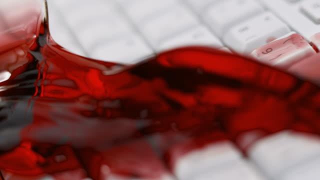 SLO MO LD glas rode wijn raken van een witte toetsenbord en het morsen van wijn op de toetsen