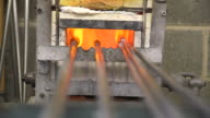 Glass on the end of blowpipes is heated in a furnace, UK.