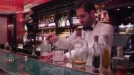 Glass with a cube of ice sits on the bar at the Park Chinois restaurant in Mayfair London United Kingdom on Friday Jan 22 Bar man pours a measure of...