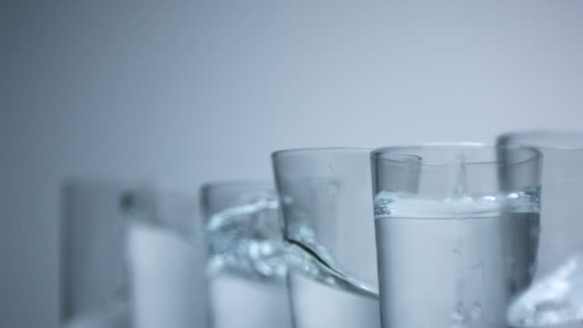 Glasses filled with water, slow motion