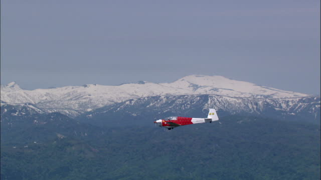 A glider soars above a forest near a snow-capped mountain in Hokkaido, Japan.