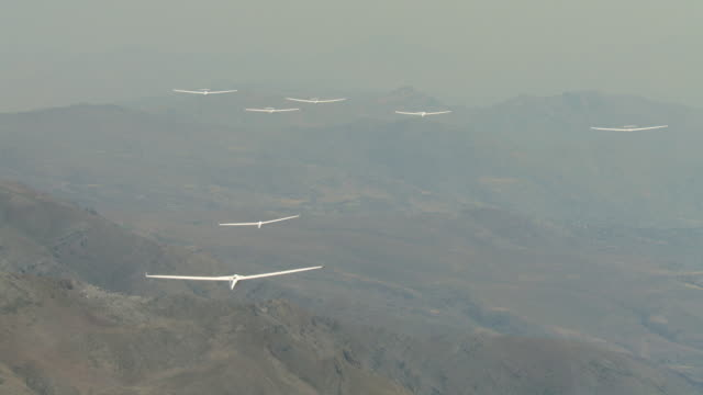 2010 AERIAL Gliders flying in the haze over barren, rocky mountains / Santiago de Chile, Gran Santiago, Chile
