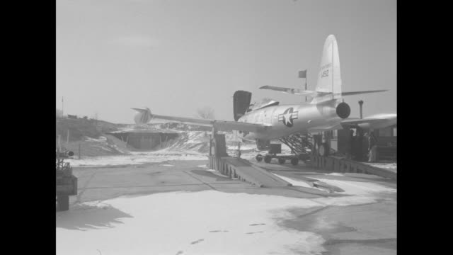 CU gloved hand holds open badge holder inscribed 'Schmidt 3' with snowy airfield in background / WS factory workers stand atop an F84 Thunderjet on a...