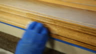Gloved Hand Staining Oak Window Trim