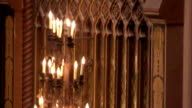 Glowing candelabras hang in front of a gilded wood panel inside an art deco cinema, Tooting. Available in HD.