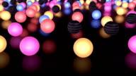 Raggiante palline colorate in movimento lento sul piano riflettente