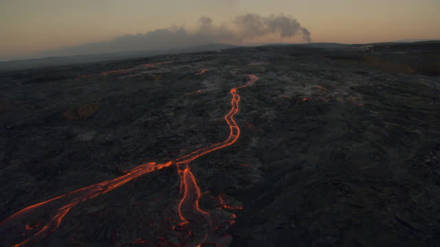 Glowing lava flows from volcano at dawn, Hawaii