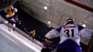 CANTED REAR VIEW goalie trying to stop scoring puck being shot by other team players