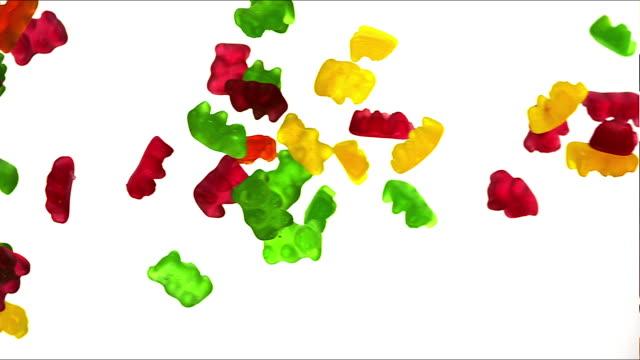 'Gold Bears or Gummy Bears falling against White Background, Slow Motion'
