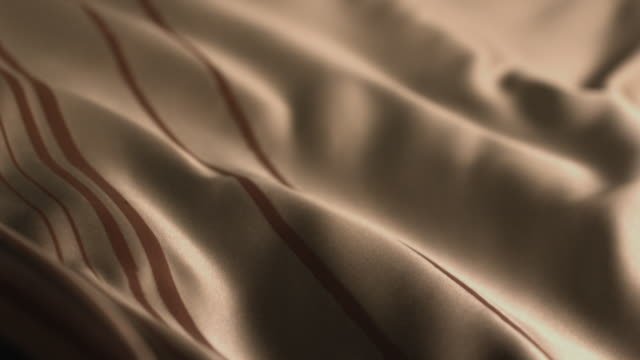 Gold coloured silk scarf moving like waves from gentle wind.