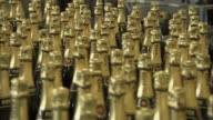 CU PAN Gold topped champagne bottles moving in different directions on conveyor belts / Reims, Champagne, France