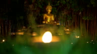 Golden Buddha Statue in Meditation Sitting Pose with Grass and Candle