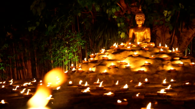 Golden Buddha Statue in sitting pose with candles