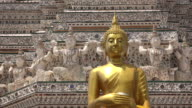 Golden buddha statue standing in front of building at Wat Arun in Bangkok, Thailand