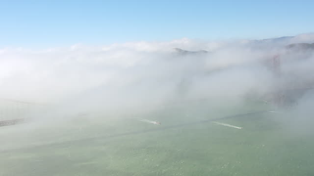 WS AERIAL POV Golden Gate Bridge covered with fog / San Francisco, California, United States