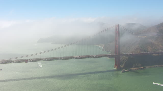 WS AERIAL POV Golden Gate Bridge with fog, coastline in background / San Francisco, California, United States