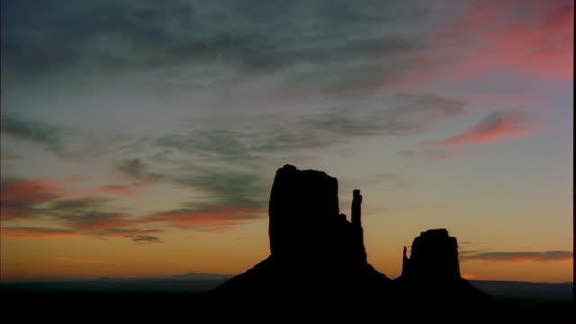 A golden hour sky surrounds the West and East Mitten buttes in Monument Valley, Utah.