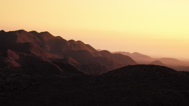 Golden light glows above the hills of the Kalahari Desert. Available in HD.