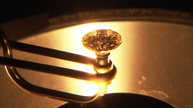 A golden light glows on a diamond rotating on a machine.