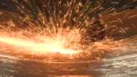 Golden sparks spray in a circle as a worker uses a grinder on a sheet of steel. Available in HD.